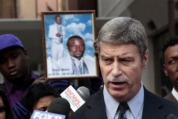 Jim Letten with Glover photo behind him